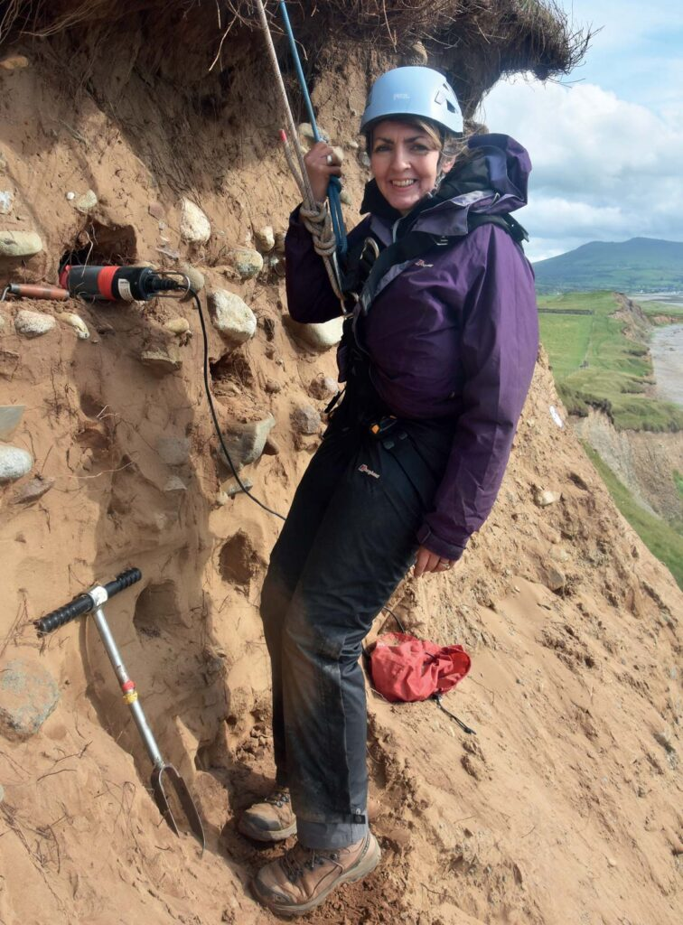 Helen Roberts taking samples for Optically Stimulated Luminesence dating during our rope-access excavation of the eroding cliff face in June 2019.