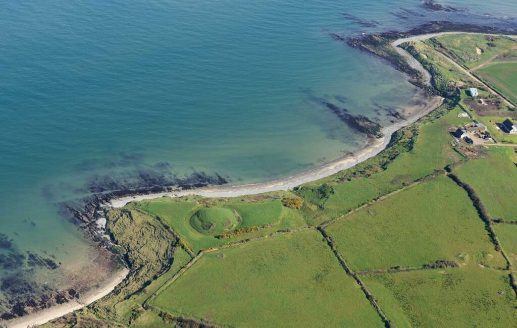 Oblique aerial photograph of Glascarrig motte and bailey site with associated deserted settlement. The site is actively being eroding by the sea.