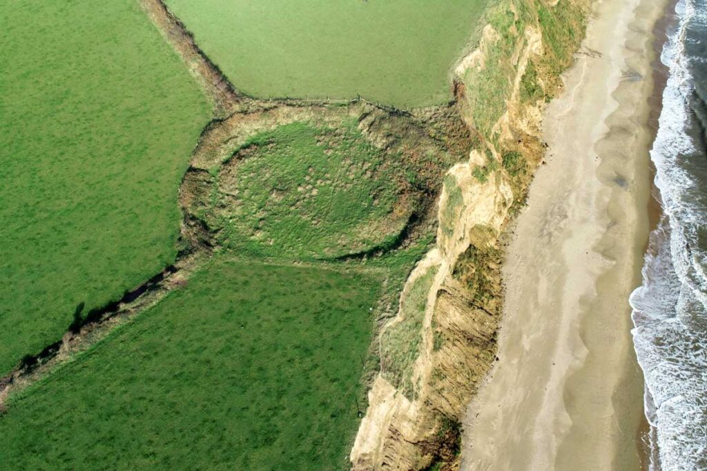 Oblique aerial photograph of the ringfort at Killincooley Beg with its eastern banks eroding into the soft sediment sea cliffs