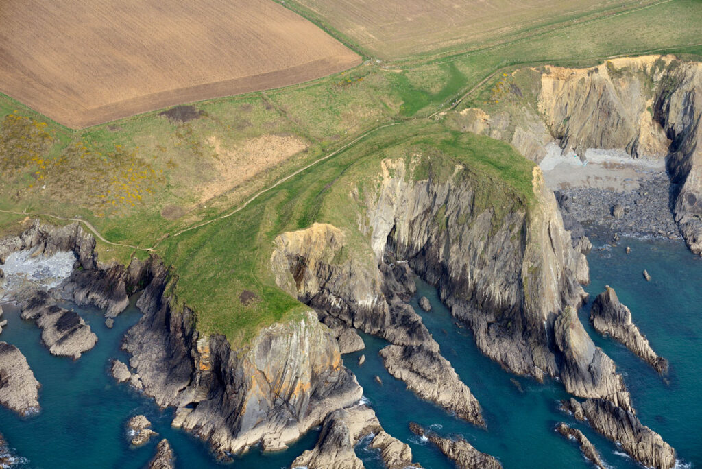 Aerial photograph of Porth y Rhaw. Visible are the series of banks and ditches that enclose the central eroded chasm and the eastern promontory.