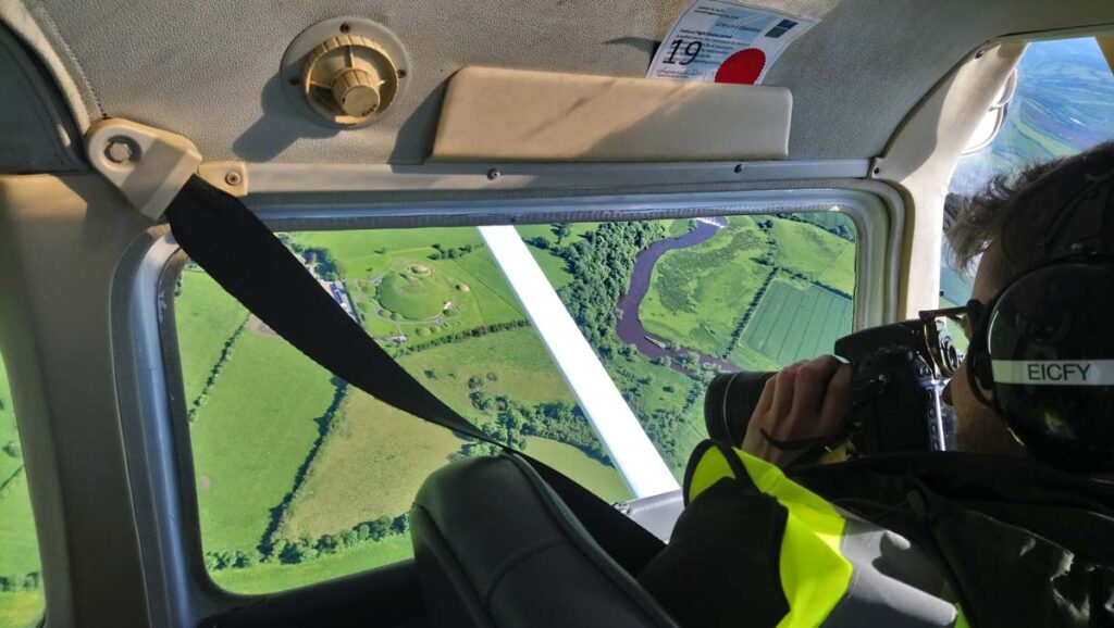 Participant of the CHERISH flying school landing capturing an oblique image of Brú na Bóinne through the open window of the cockpit.