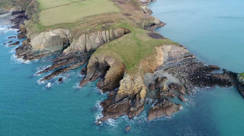 An aerial photograph taken by UAV of Caerfai Camp promontory fort showing its substantial defences formed of a series of four banks and ditches. Much of the large interior still survives but coastal erosion will eventually cut-off much of the promontory fort from the mainland, forming a new island.