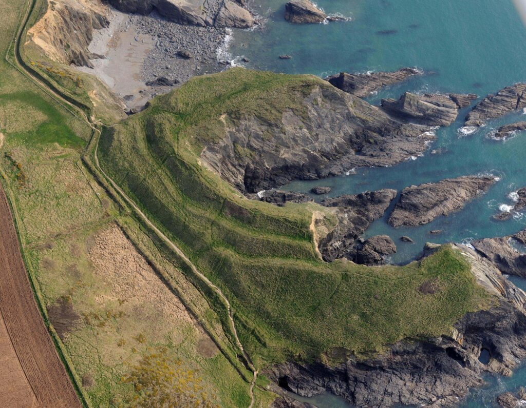 An aerial photograph of Porth y Rhaw promontory fort taken from a manned aircraft showing its series of enclosing defences and heavily eroded interior. Evidence of roundhouses was discovered through excavation in the eastern portion of the surviving interior (top of picture).