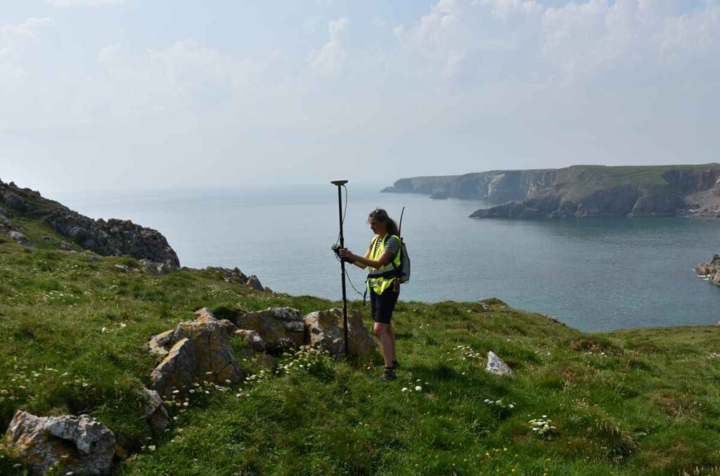 Louise Barker surveying the rampart at Crocksydam, with Flimston Bay fort in the distance
